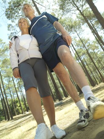 tilt view: Senior couple in sportswear standing in clearing in wood, smiling, low angle view (tilt)