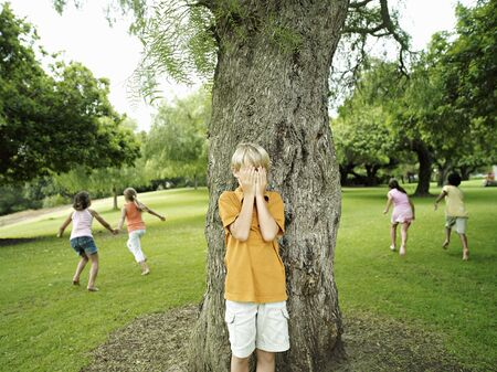 hands covering eyes: Boy (7-9) with hands covering eyes playing hide and seek in park, hiding from friends behind tree