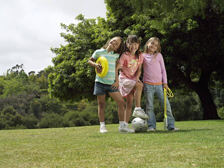 three people only: Three girls (7-9) standing on grass in park with frisbee, soccer ball and skipping rope, portrait