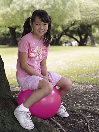 hopper: Girl (7-9) sitting on pink space hopper beneath tree in park, smiling, side view, portrait LANG_EVOIMAGES