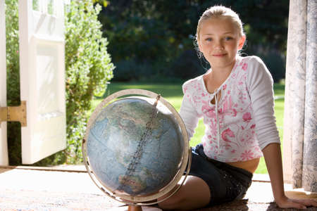 french doors: Girl (8-10) sitting with globe by French doors, smiling, portrait