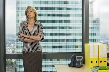 one mid adult woman only: Blonde businesswoman standing beside office window, arms folded, smiling, front view, portrait LANG_EVOIMAGES