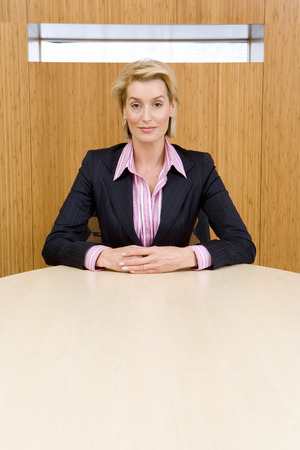 hands clasped: Businesswoman at conference table, hands clasped, portrait