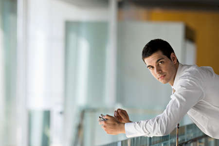 electronic organiser: Businessman leaning on glass surface, holding personal electronic organiser, side view, portrait