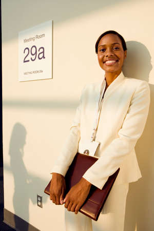 nametag: Businesswoman, in white suit, standing outside meeting room with folder, smiling, portrait