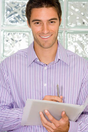 glass block: Businessman with pen and paperwork by glass block wall, smiling, portrait, close-up LANG_EVOIMAGES