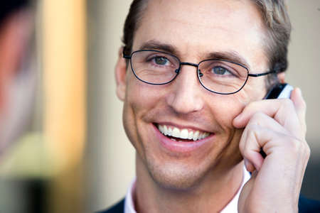differential focus: Businessman in spectacles using mobile phone, smiling, close-up (differential focus)