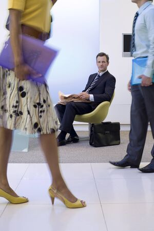 foyer: Businessman and woman walking in foyer by businessman in chair with newspaper, low section (blurred motion)