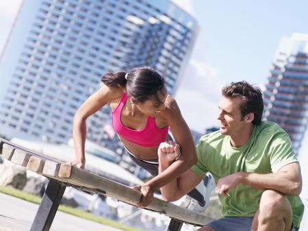 Couple exercising in park, woman doing press-ups on bench, man offering encouragement, smiling (tilt)