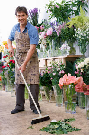 one mid adult man only: Male florist in apron standing in flower shop, sweeping floor with broom, smiling, portrait
