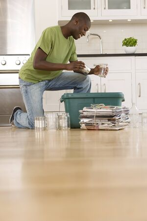 bundling: Young man putting can and glass jar into recycling bin in kitchen, ground view