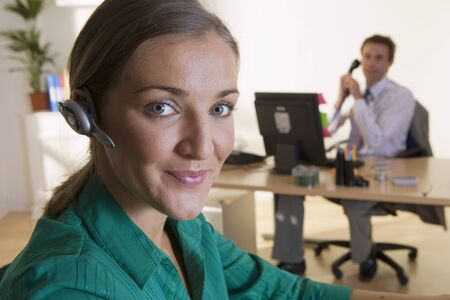 handsfree device: Man at desk in office, using telephone, focus on businesswoman with hands-free device in foreground