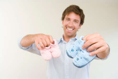 differential focus: Young man holding baby slippers, smiling, close-up of hands (differential focus)