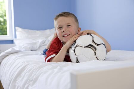 seven year old: Seven year old boy lying on bed resting chin on football in bedroom