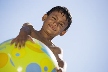 unusual angle: Boy (7-9) holding green beach ball, smiling, portrait, upward view, unusual angle LANG_EVOIMAGES