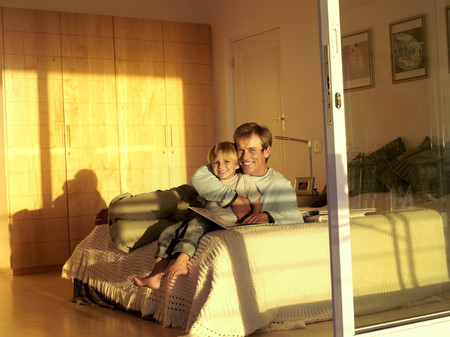 sliding doors: Father and son (5-7) sitting on bed with photo album, smiling, portrait, view through sliding doors