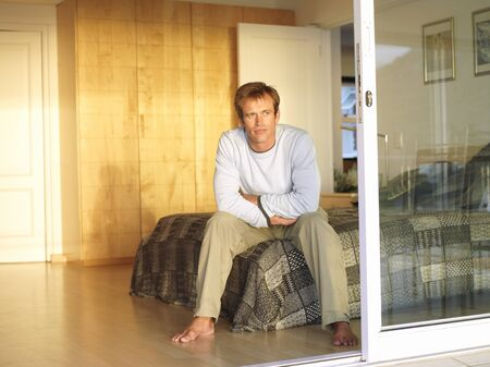 sliding doors: Man sitting on edge of double bed, thinking, view through open sliding doors