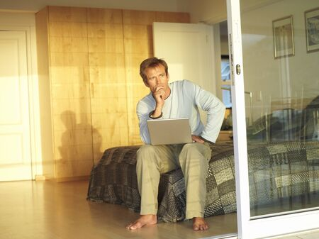 sliding doors: Man sitting on edge of bed, using laptop, hand on chin, thinking, view through open sliding doors