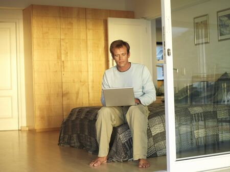 sliding doors: Man sitting on edge of double bed, using laptop, view through open sliding doors LANG_EVOIMAGES