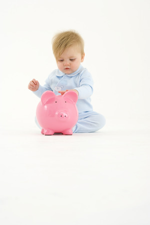 Baby boy (3-6 months) playing with piggy bank Stock Photo