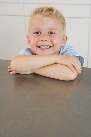 kitchen bench: Boy (2-4) resting chin on arms on kitchen bench, smiling