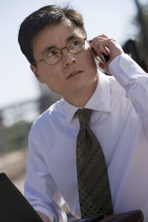 tilt view: Businessman in spectacles using laptop and mobile phone, outdoors, side view (tilt)