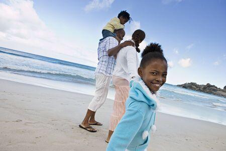 two generation family: Two generation family walking on sandy beach, girl (7-9) smiling, side view, portrait (tilt) LANG_EVOIMAGES