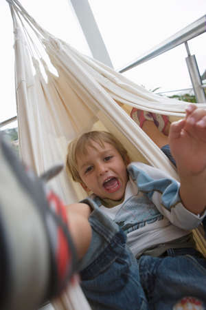 tilt view: Boy (6-8) lying in hammock, mouth open, front view, close-up, portrait (blurred motion, tilt)