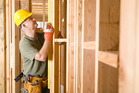 home construction: Builder in hardhat measuring beam, side view