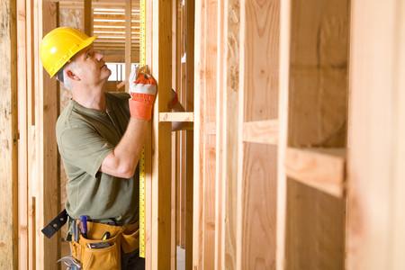 Builder in hardhat measuring beam, side view