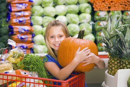 large pumpkin: Girl (7-9) standing in vegetable section of supermarket, clutching large pumpkin, smiling, portrait
