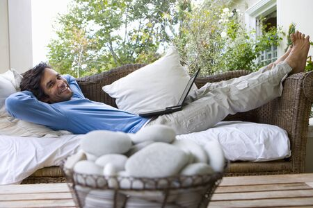 differential focus: Man lying on sofa with laptop on lap, smiling, portrait, bowl of pebbles in foreground (differential focus)