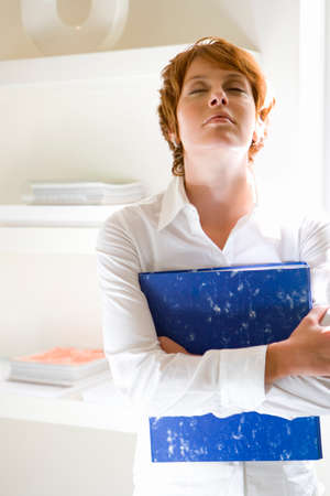 wearying: Businesswoman with folder, head back, eyes closed, close-up