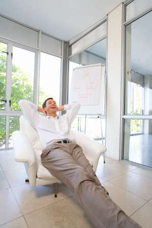 arms behind head: Businessman stretched out in armchair, arms behind head, low angle view