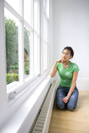 kneeling woman: Young woman with paintbrush kneeling on floor, looking at window LANG_EVOIMAGES
