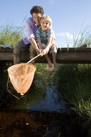 Father and son (6-8) fishing above stream on small wooden footbridge, boy holding fishing net, smiling, portrait Stock Photo