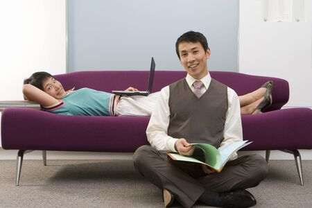 Businessman with legs crossed on floor by woman lying on sofa using laptop, smiling, portrait Stock Photo
