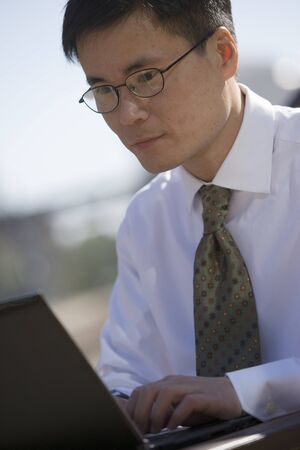 tilt view: Businessman in spectacles using laptop, outdoors, side view, close-up (tilt)
