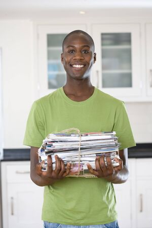 bundling: Young man with bundle of newspapers, smiling, portrait