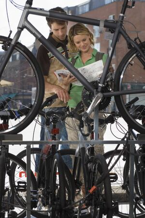 looking through frame: Young couple shopping for new bike in bicycle shop, looking at brochure, view through bike frame