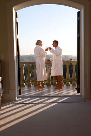 bath robes: Mature couple wearing white bath robes, standing on balcony with drinks, view through doorway