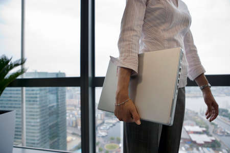 midsection: Businesswoman standing beside window, carrying laptop underarm, side view, mid-section