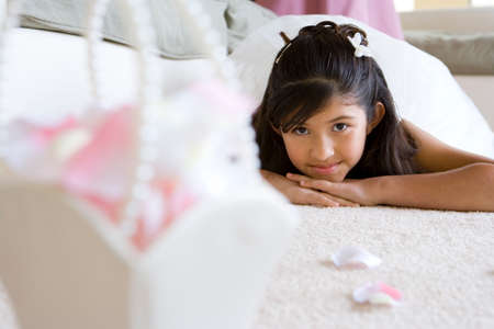 Girl (8-10), in bridesmaid's dress, lying face down on carpet in living room, wedding gift in foreground, focus on girl, smiling, front view, portrait (surface level)