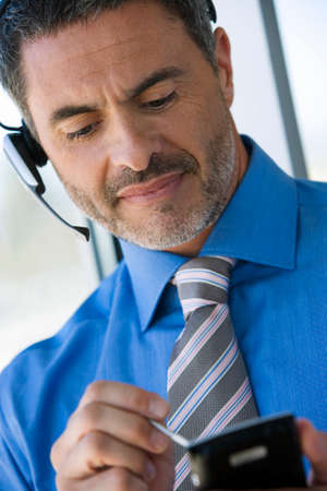 electronic organiser: Businessman wearing telephone headset, using personal electronic organiser, close-up (tilt) LANG_EVOIMAGES