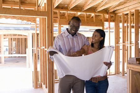 Junge Paare, die Blaupausen in teilweise gebautes Haus, lächelnd