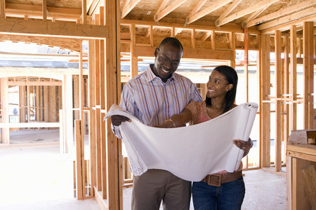 buying house: Young couple looking at blueprints in partially built house, smiling