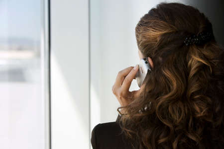 looking through window: Businesswoman using mobile phone, looking through window, close-up, rear view LANG_EVOIMAGES