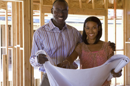 Young couple with blueprints in partially built house, smiling, portrait Stock Photo