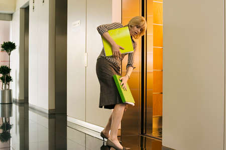 only mid adult women: Businesswoman entering office elevator, struggling to keep hold of folders, side view LANG_EVOIMAGES