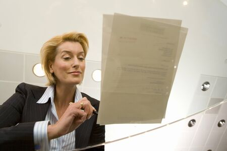low glass: Businesswoman signing paperwork on glass table, low angle view through glass